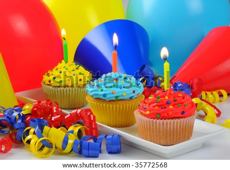 Colorful birthday cupcakes with lit candles.