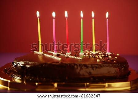 Colorful birthday light candles in a chocolate cake red background - stock photo