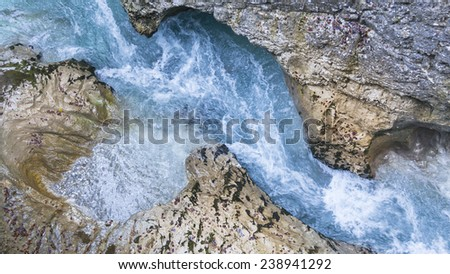 Colorful blue river with water flowing on the rocky terrain. - stock photo