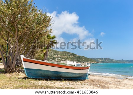 Colorful boat lying on greek beach with blue sea and sky - stock photo