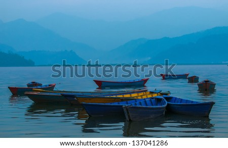 Colorful boats in Phewa Lake in Pokhara, Nepal - stock photo