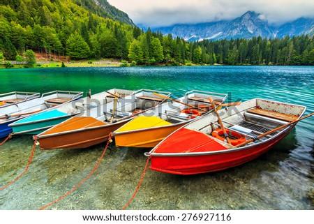 Colorful boats on the crystal clear alpine lake,near Slovenian-Italy border,Lake Fusine,Italy,Europe - stock photo