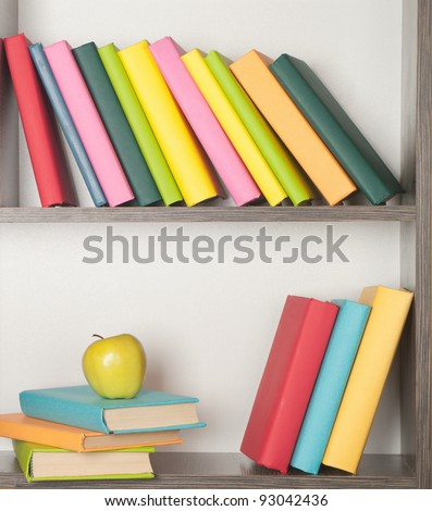 colorful book and apple and  on the bookshelf - stock photo