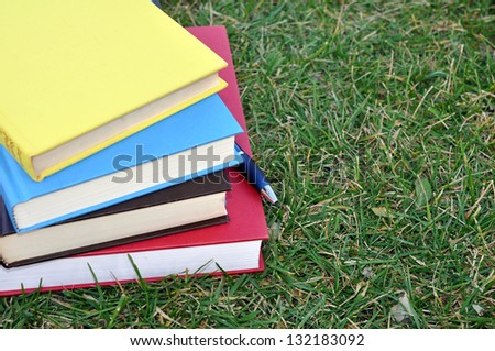 colorful books on grass in campus