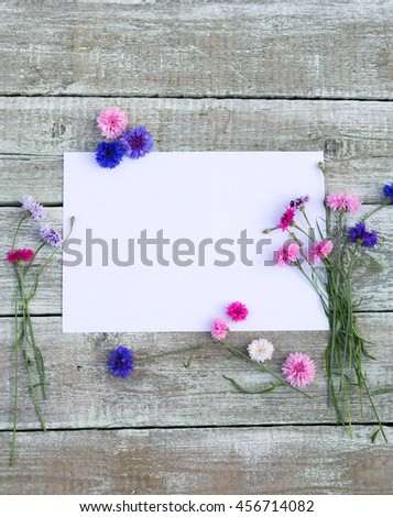 Colorful bouquet of summer garden flowers. Cornflowers with blank paper for greeting message on old shabby wooden table. Vintage floral background. Floral mock up with multicolored flowers. Copy space - stock photo