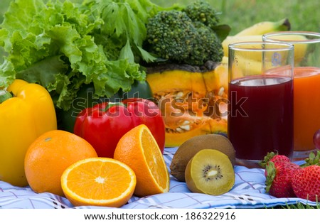 Colorful bowl of tropical fruit salad with Orange  kiwifruit and fruit juice at the picnic in the grass  - stock photo
