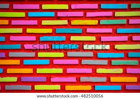 Colorful brick wall painted in yellow pink white and blue