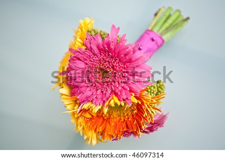 Colorful bridesmaid's bouquet with pink, yellow, and orange flowers. - stock photo