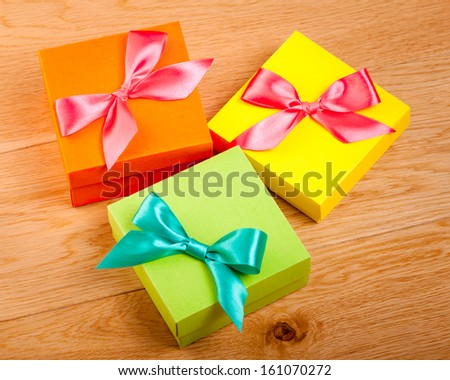 Colorful bright gift boxes on wooden background - stock photo