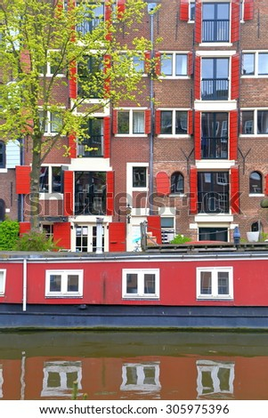 Colorful buildings and old house boat reflected by the canal water in Jordaan district, Amsterdam, Holland