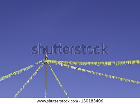 Colorful bunting flags against blue sky - stock photo
