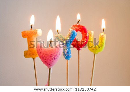 Colorful burning candles making confesson 'I love you' - stock photo
