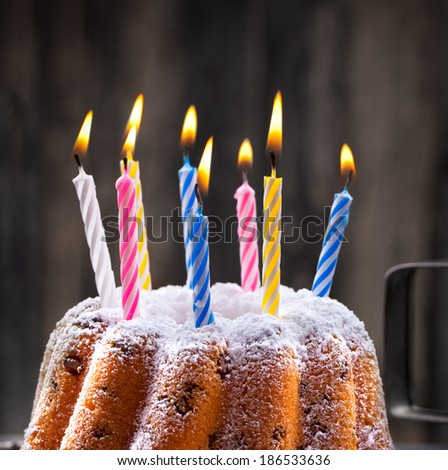colorful burning candles on a birthday cake on dark background - stock photo