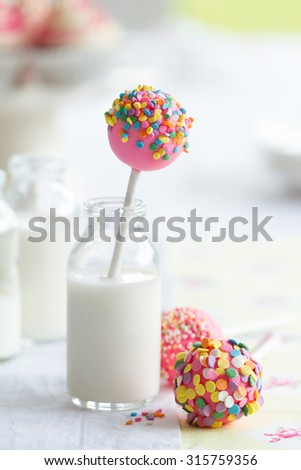 Colorful cake pops and milk - stock photo