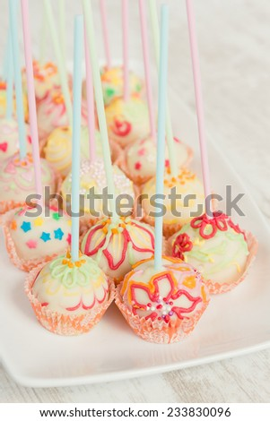 Colorful cake pops on white plate