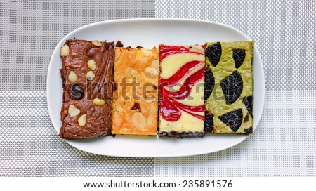 Colorful cakes on white plate and grey table mat - stock photo