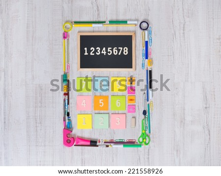 Colorful calculator composed of assorted stationery objects and stick notes. - stock photo