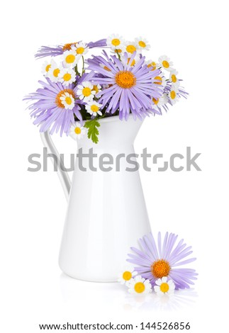 Colorful camomile flowers in jug. Isolated on white background - stock photo