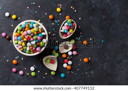 Colorful candies and chocolate egg on stone background. Top view - stock photo