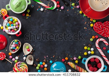 Colorful candies and coffee cup frame on stone background. Top view with copy space - stock photo
