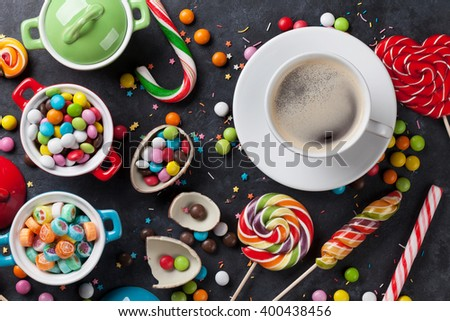 Colorful candies and coffee cup on stone background. Top view - stock photo