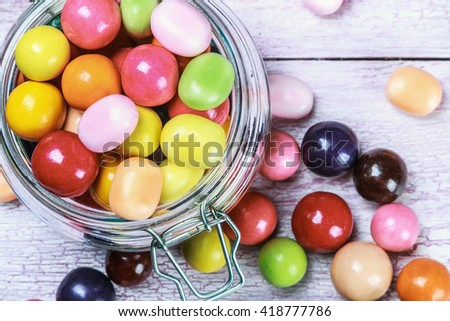 Colorful candies and lollipops in a jar on wooden background. focus on sweets and a glass jar - stock photo