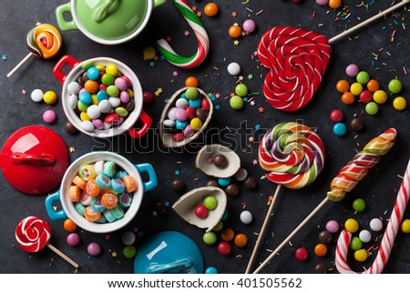 Colorful candies and lollypops on stone background. Top view - stock photo