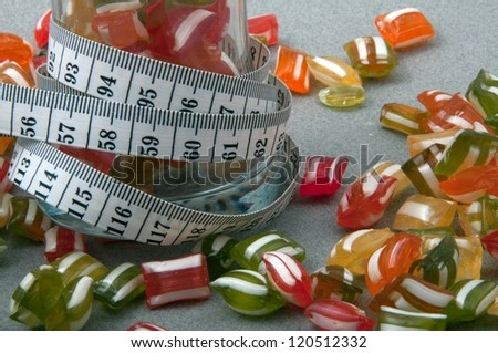 colorful candies and white tapeline - stock photo