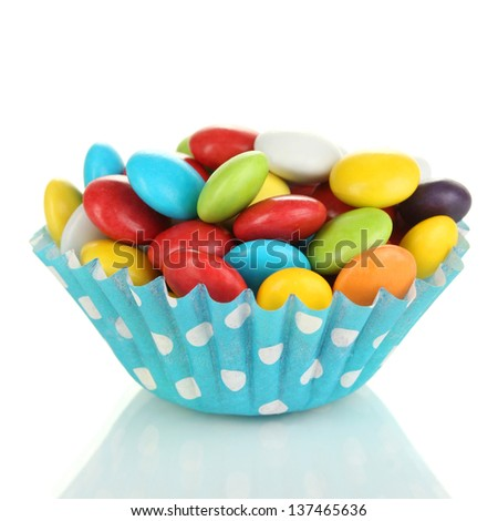 Colorful candies in cupcake case isolated on white - stock photo