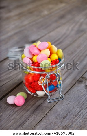 Colorful candies in small jar on the wooden table - stock photo