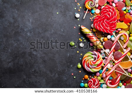 Colorful candies, jelly and marmalade over stone background. Top view with copy space - stock photo