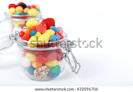 Colorful candy and gum in the glass jar close up on a white background with copy space