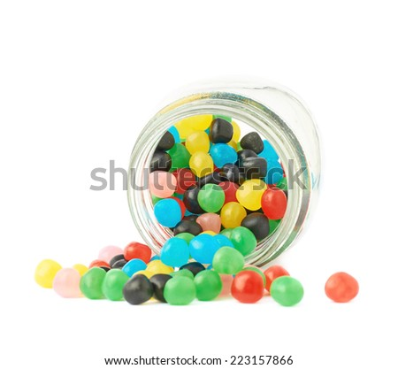Colorful candy ball sweets falling out of a glass jar, composition isolated over the white background