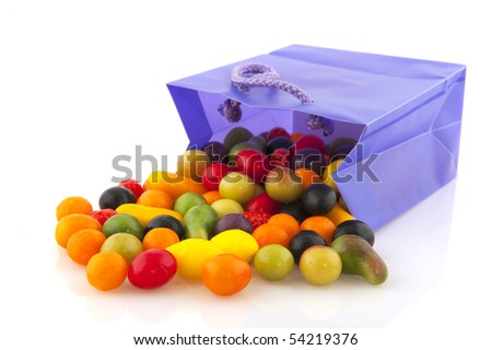 Colorful candy in purple bag isolated over white
