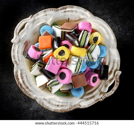 Colorful candy in rustic white dish. Liquorice allsorts in many colors and shapes. Filter effects. - stock photo