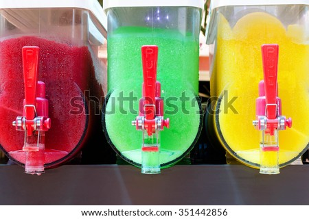 Colorful canisters of refreshing frosty cold slushy ice drinks