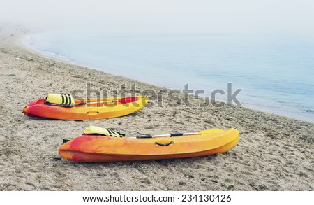 Colorful canoe boats on sea shore in thick fog early in the morning - stock photo