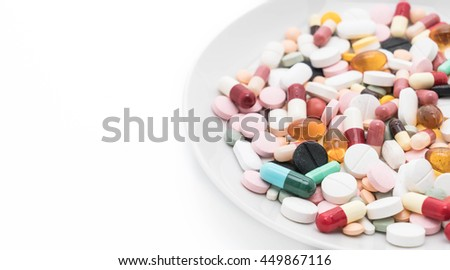 Colorful capsules and pills on plate