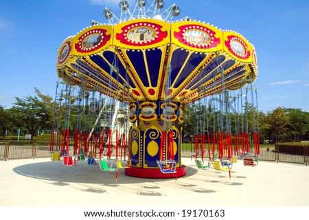 Colorful carousel in attraction park - stock photo