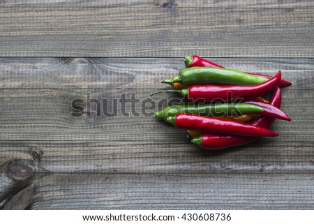 Colorful cayenne chili peppers on wooden table. - stock photo