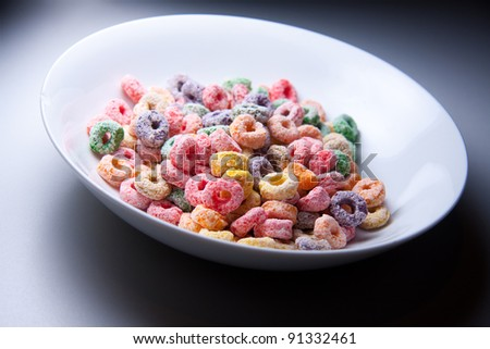 Colorful cereal on a bowl on dramatic background - stock photo