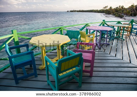 Colorful chairs and tables overlook the Caribbean Sea at a resort.