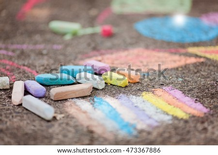 Colorful chalk and doodles on asphalt. Kids learning and education, hand drawn shapes on background. Selective focus.