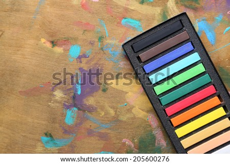 Colorful chalk pastels in box on wooden background - stock photo