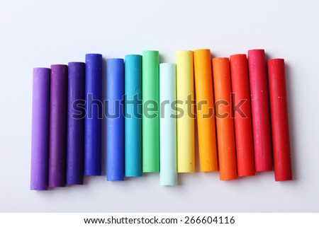 Colorful chalk pastels on white background arranged as rainbow spectrum - stock photo