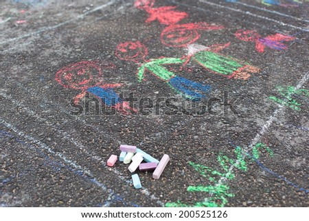 Colorful chalks on asphalt, child drawing - stock photo