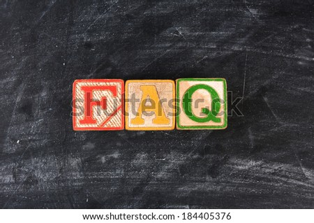 Colorful childrens blocks spelling out FAQ on a chalk board. Horizontal format. - stock photo