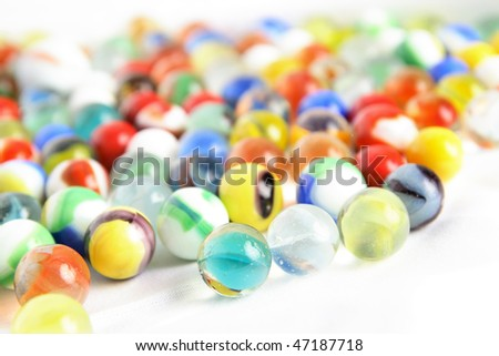 Colorful childrens' marbles assorted on a white background - stock photo