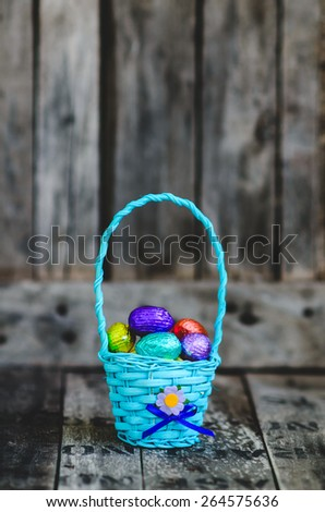 Colorful chocolate easter eggs in blue basket on wooden background. - stock photo
