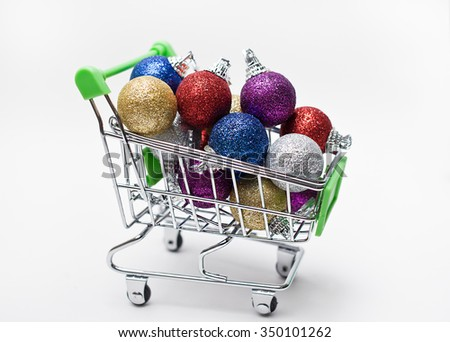 Colorful Christmas balls in a shopping cart on white background - stock photo